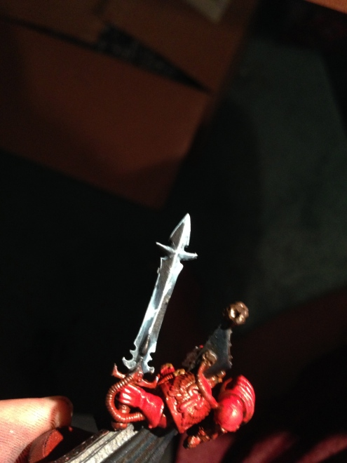 A shiny dark metallic sword collects light in specific areas. High contrast to denote high reflective properties.